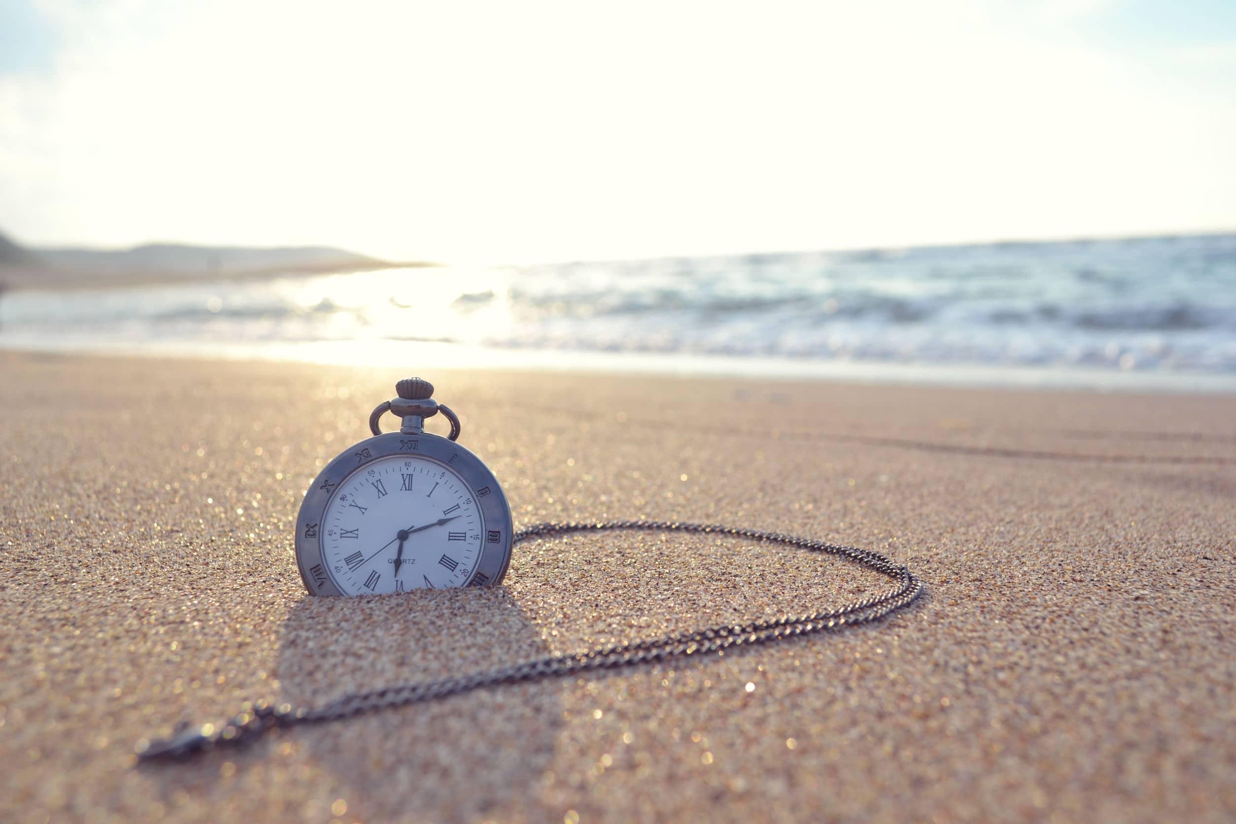 Relógio de bolso caído em areia da praia, com mar ao fundo.