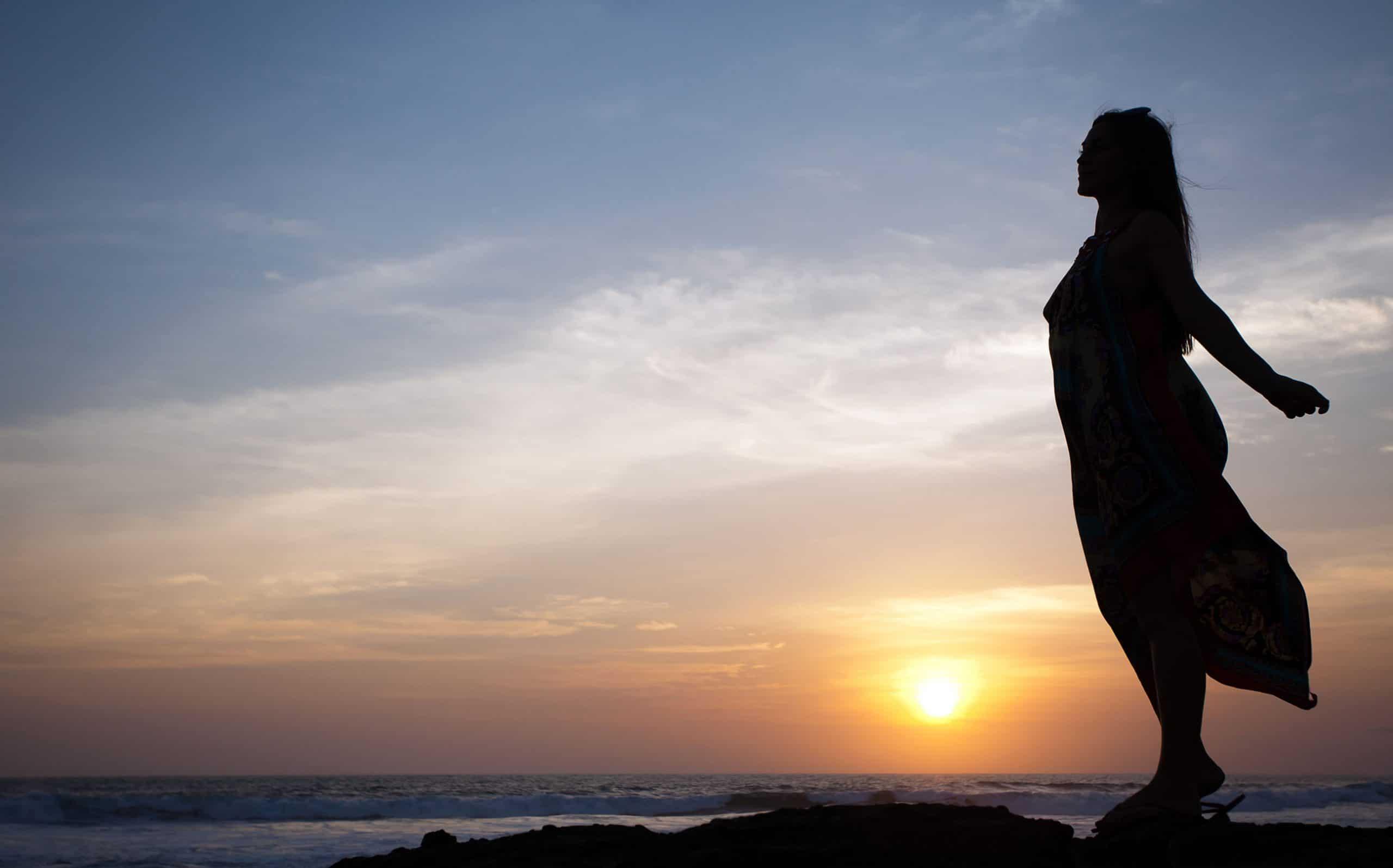 Silhueta de mulher com cabelos soltos ao vento em uma praia observando o pôr do sol.