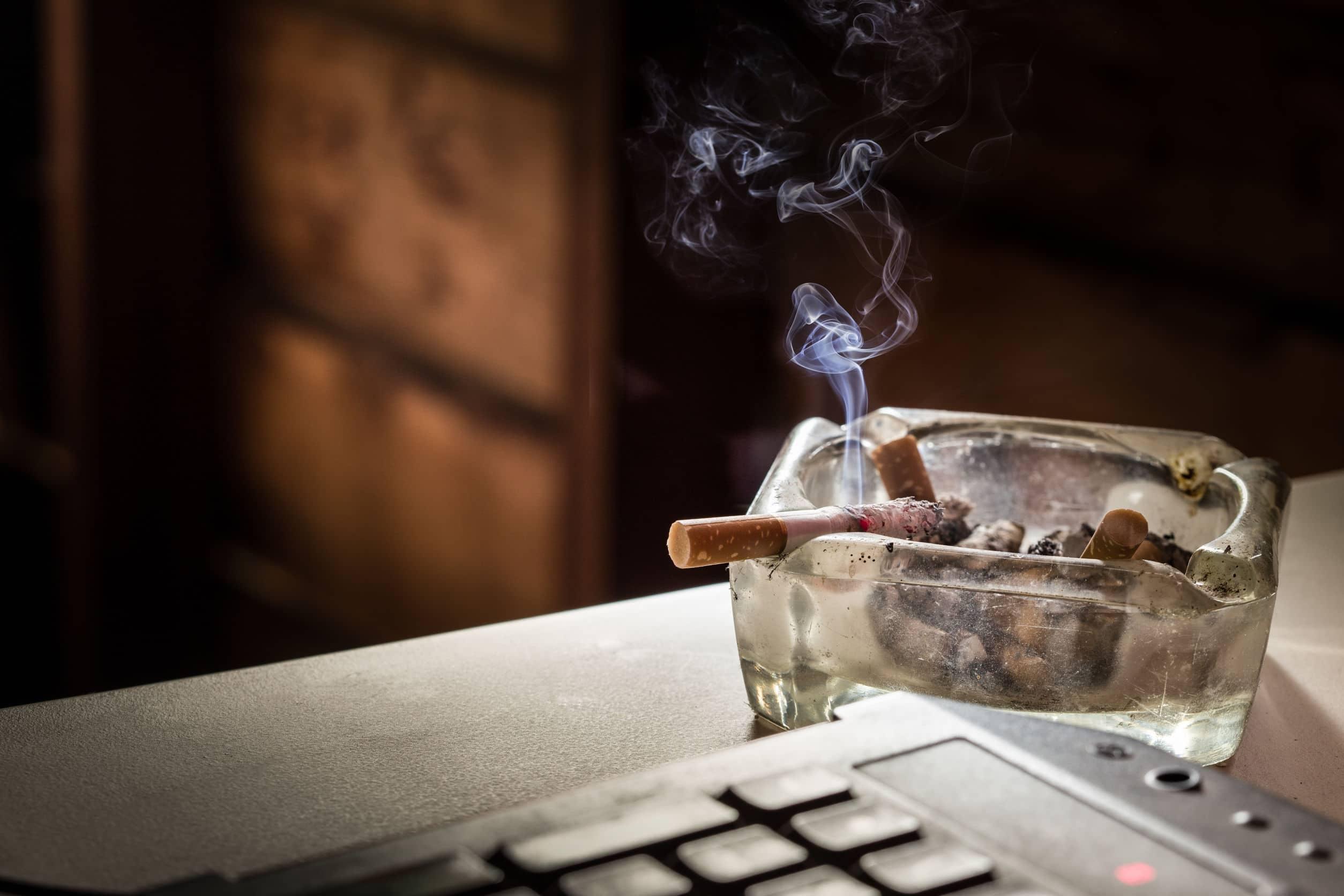 Bitucas de cigarros acesos em cinzeiro de vidro.