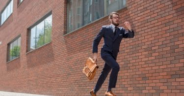 Homem vestido como executivo, de terno e pasta. Ele corre em frente à uma parede de tijolos.