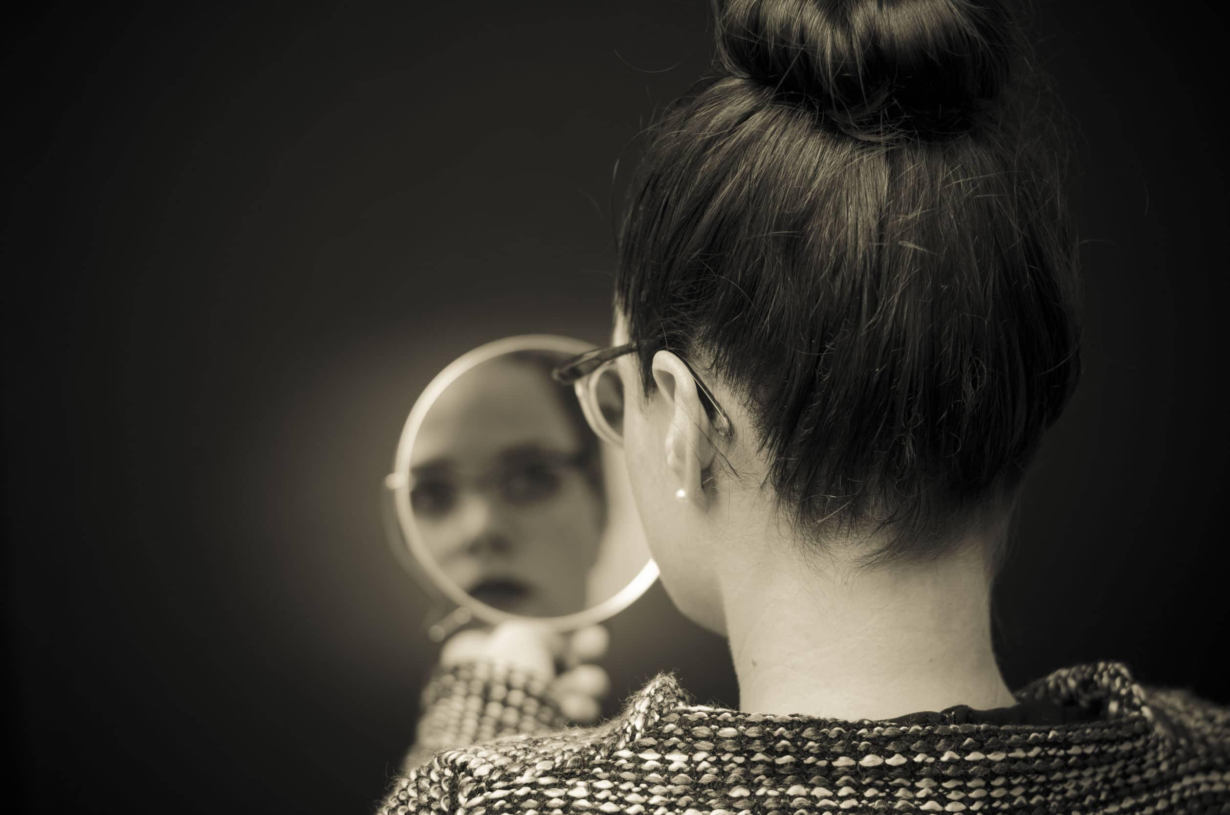 mulher olhando para auto reflexo no espelho