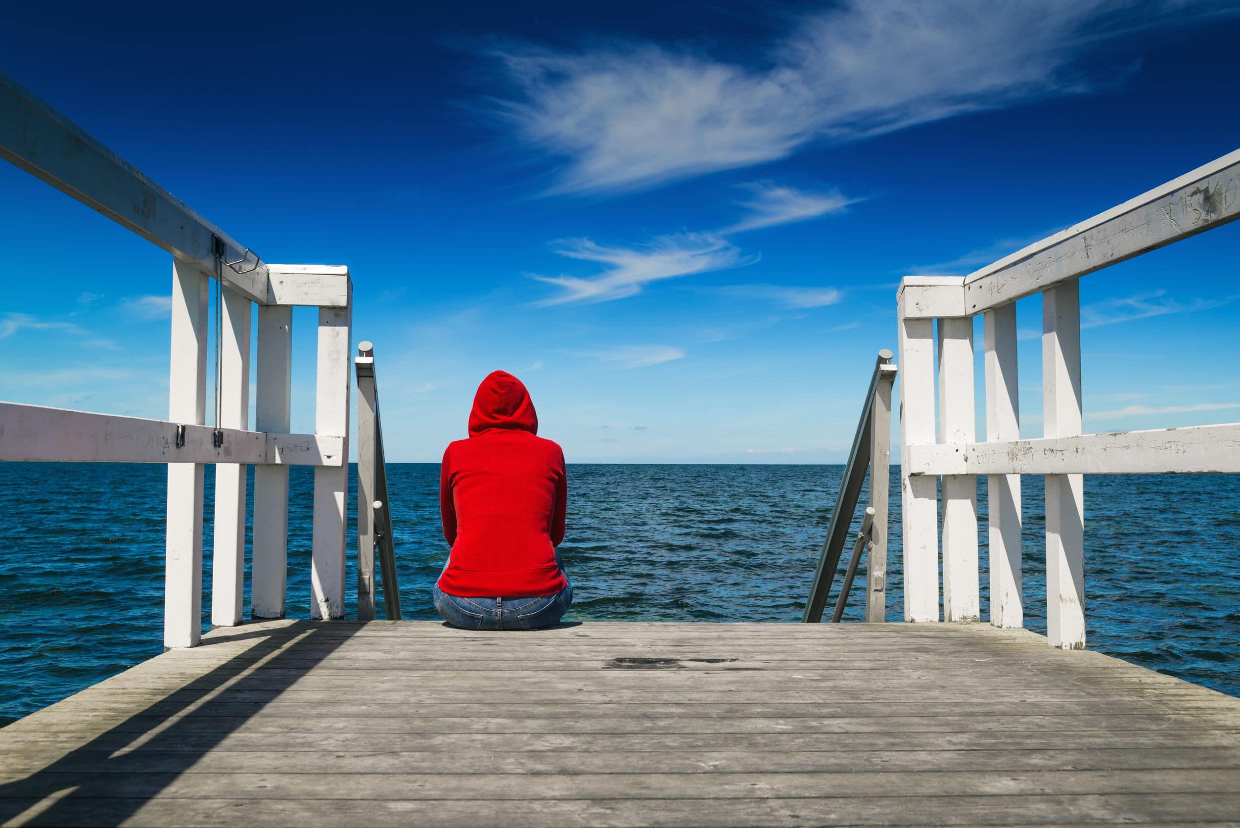 Pessoa usando um casaco vermelho sentada no cais de uma praia admirando o mar. Conceito de saudade, solidão, tristeza.