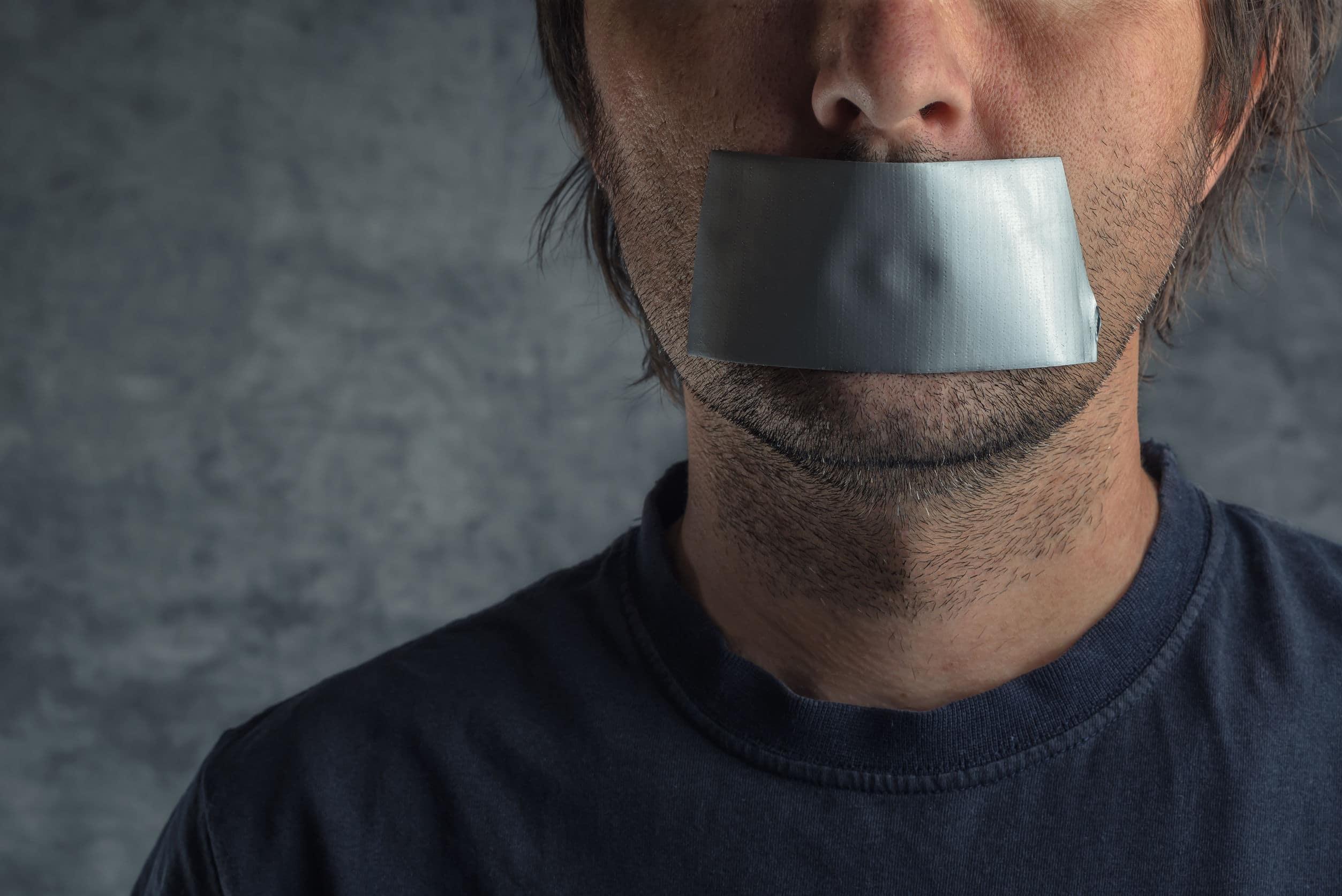 homem caucasiano adulto com fita adesiva na boca para impedi-lo de falar.