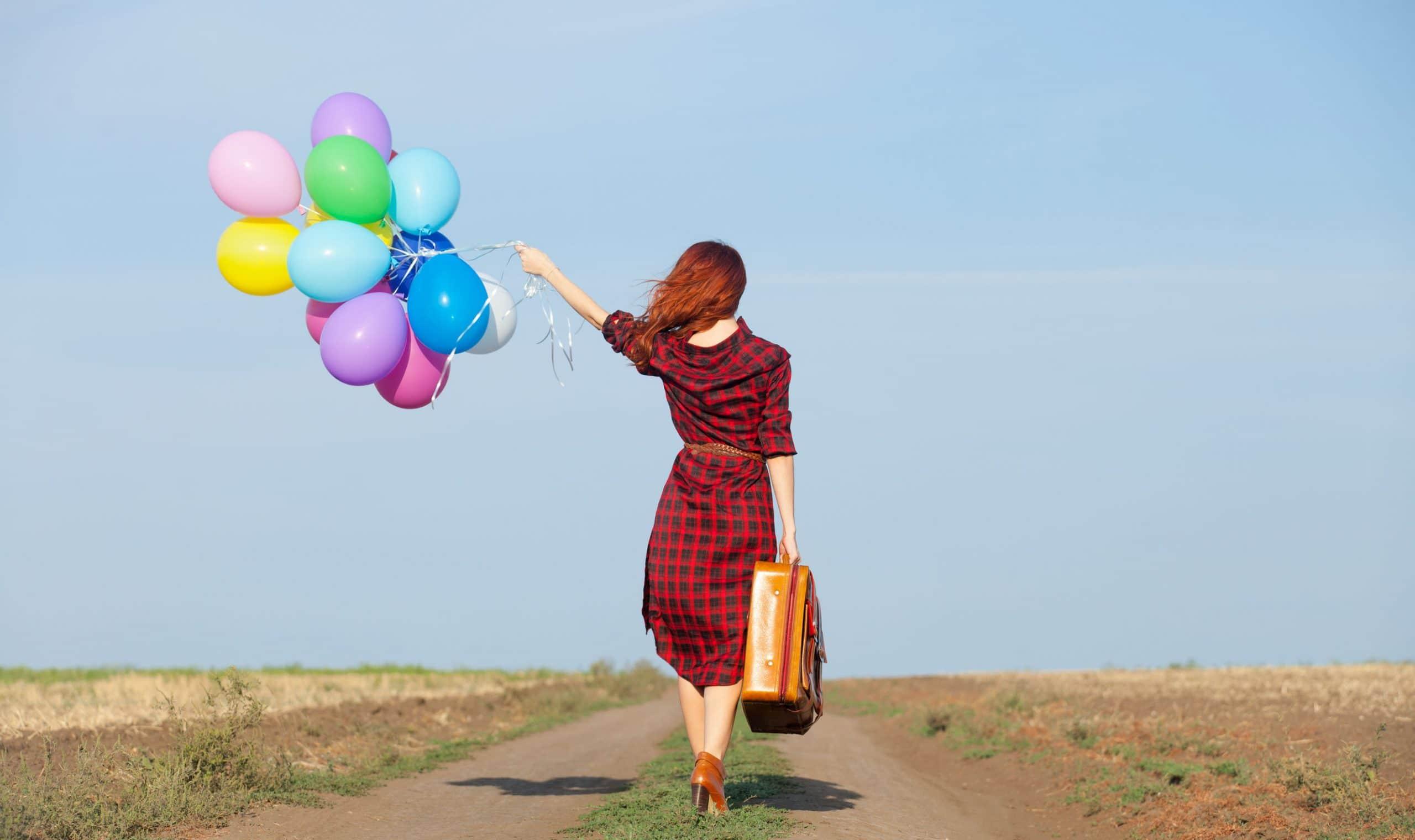 Mulher com vestido xadrez, carregando uma mala em uma mão e balões na outra mão. Ela anda em uma estrada que parece abandonada.