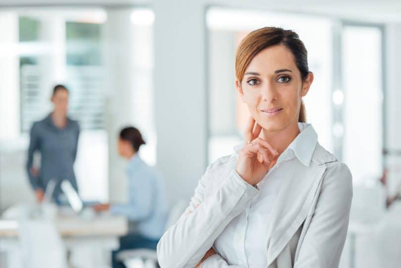 Mulher vestida com roupas sociais, em pé em sala de reuniões, sorridente.