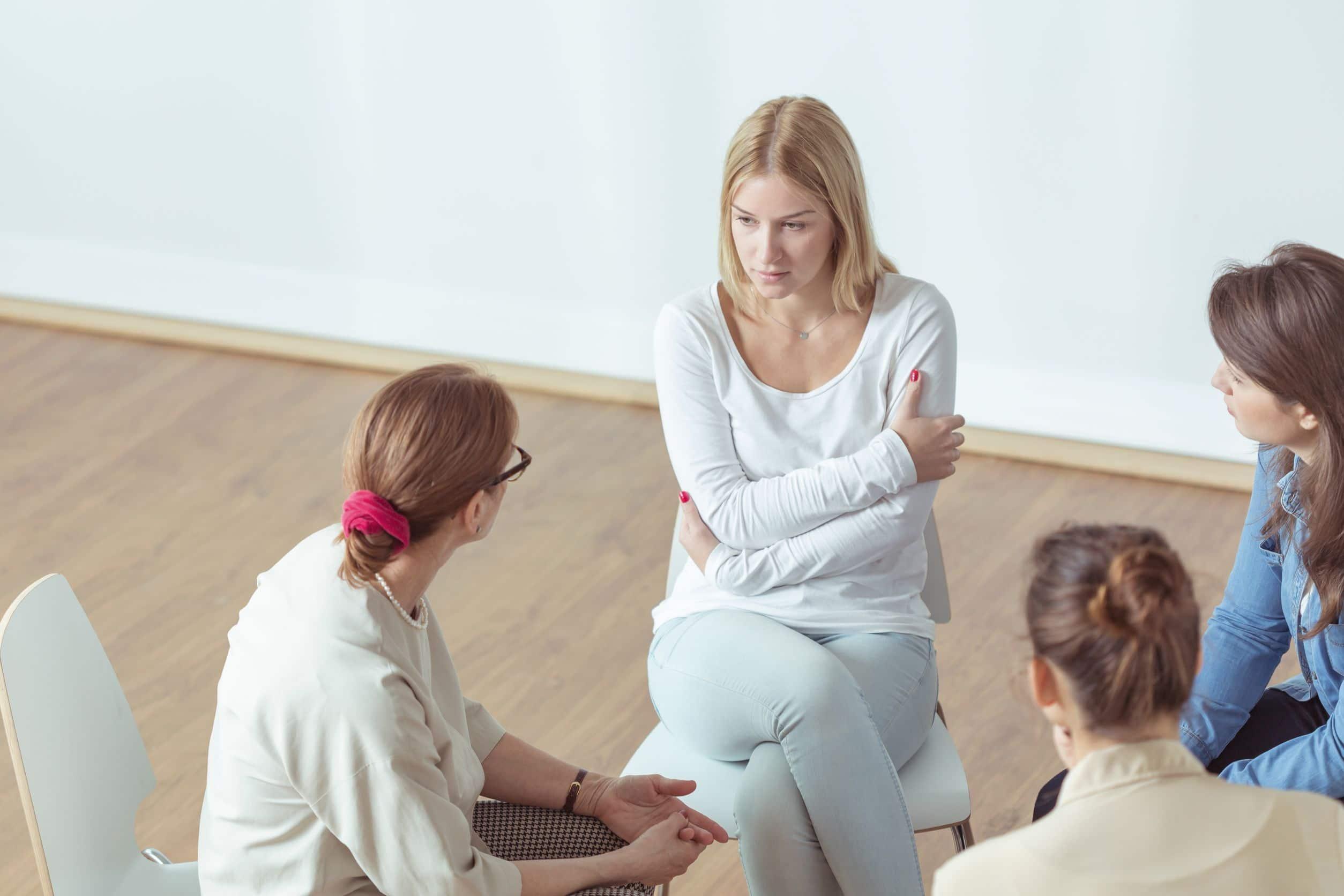 Mulher conversando com coach em terapia.