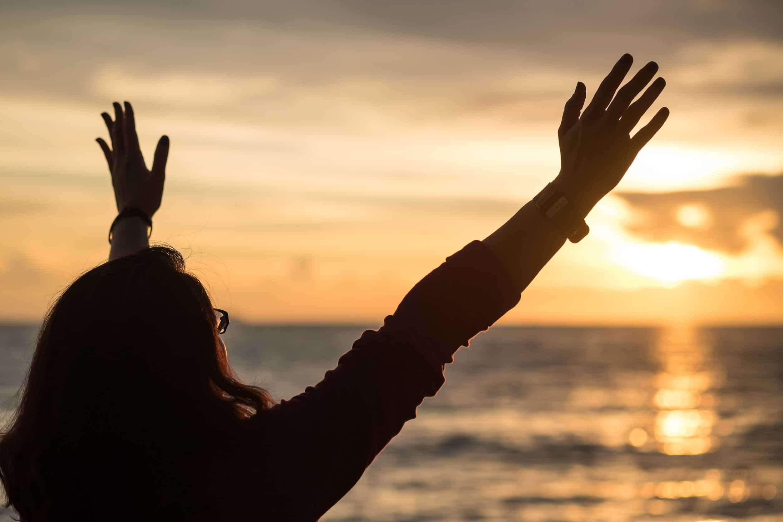 imagem de silhueta de uma mulher levantando as mãos para o céu no tempo do sol