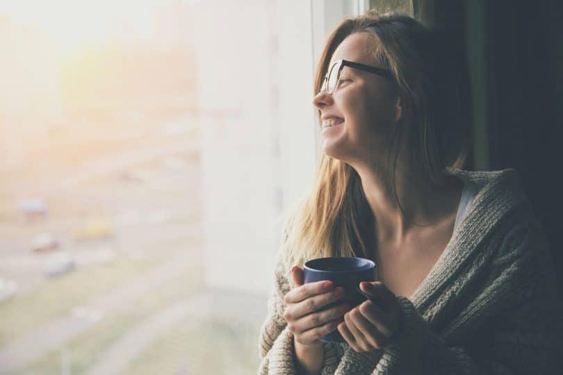 menina alegre bebendo chá no sol da manhã perto da janela.