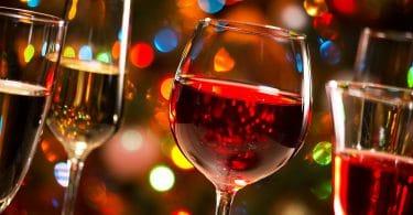 Taças de cristal de vinho e de champanhe no fundo de luzes de Natal.