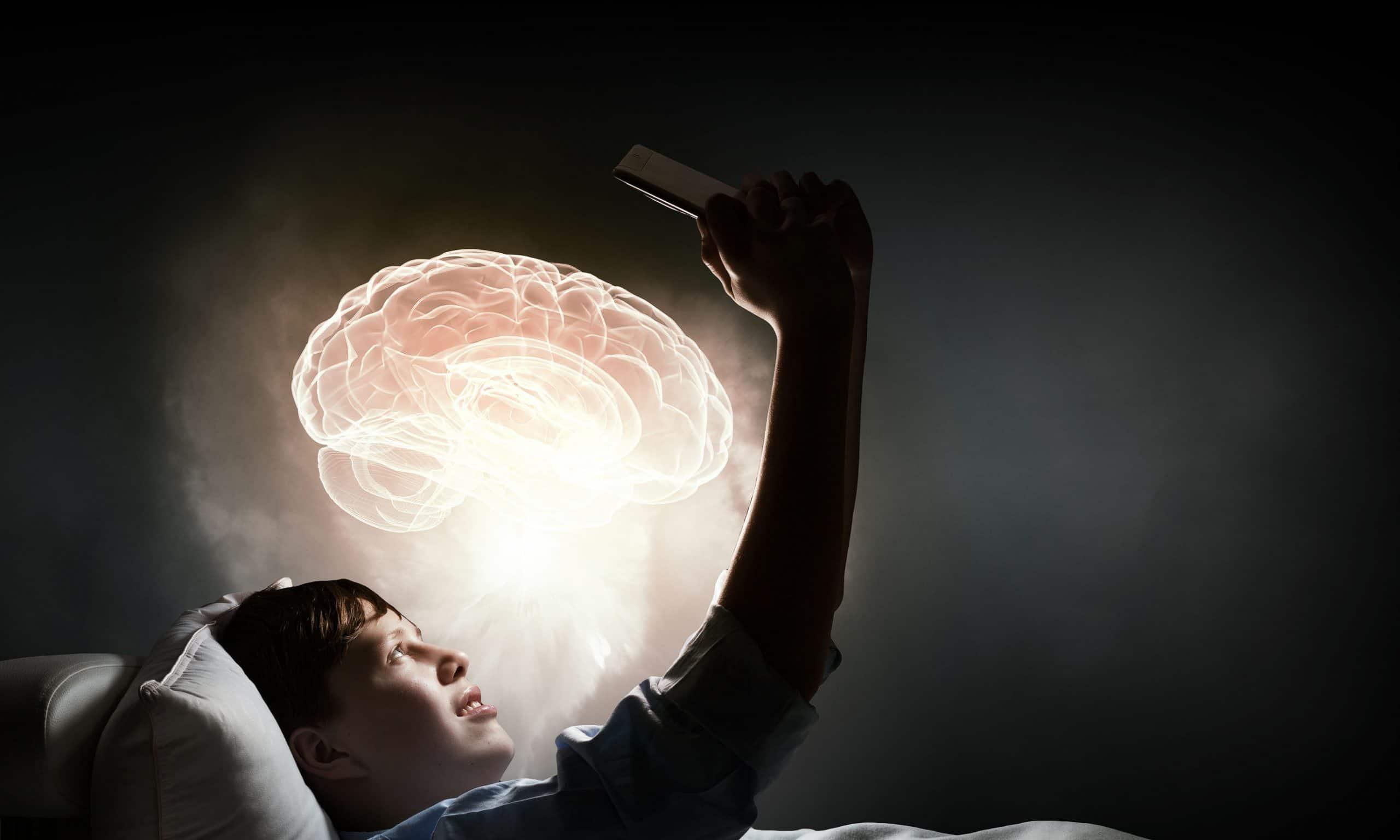 Menino deitado em sua cama lendo e tendo uma idéia. Desenho de cérebro iluminado projetado em frente ao seu rosto.