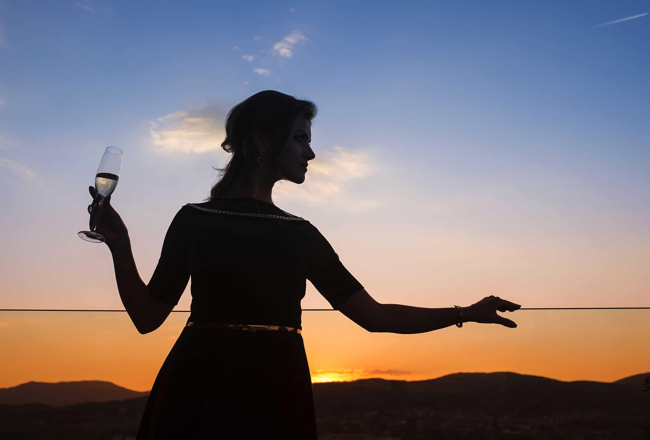 Silhueta de mulher segurando taça de champanhe em um terraço com o por do sol ao fundo.