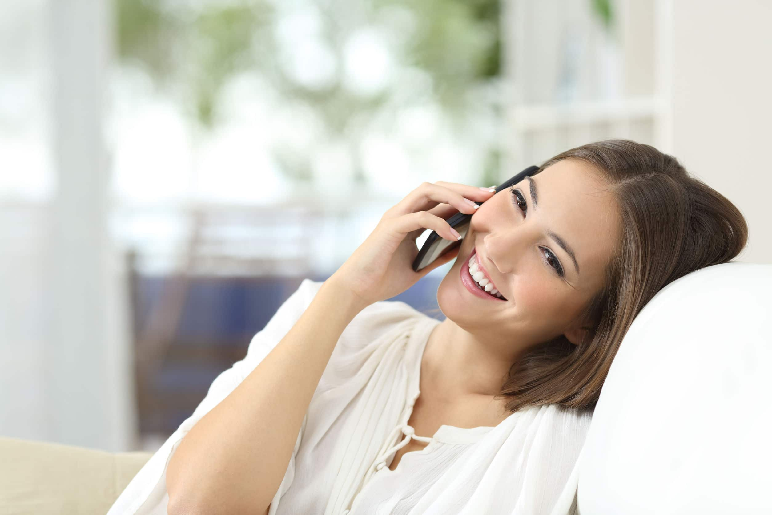 Mulher branca sorridente sentada em sofá branco enquanto fala no telefone.