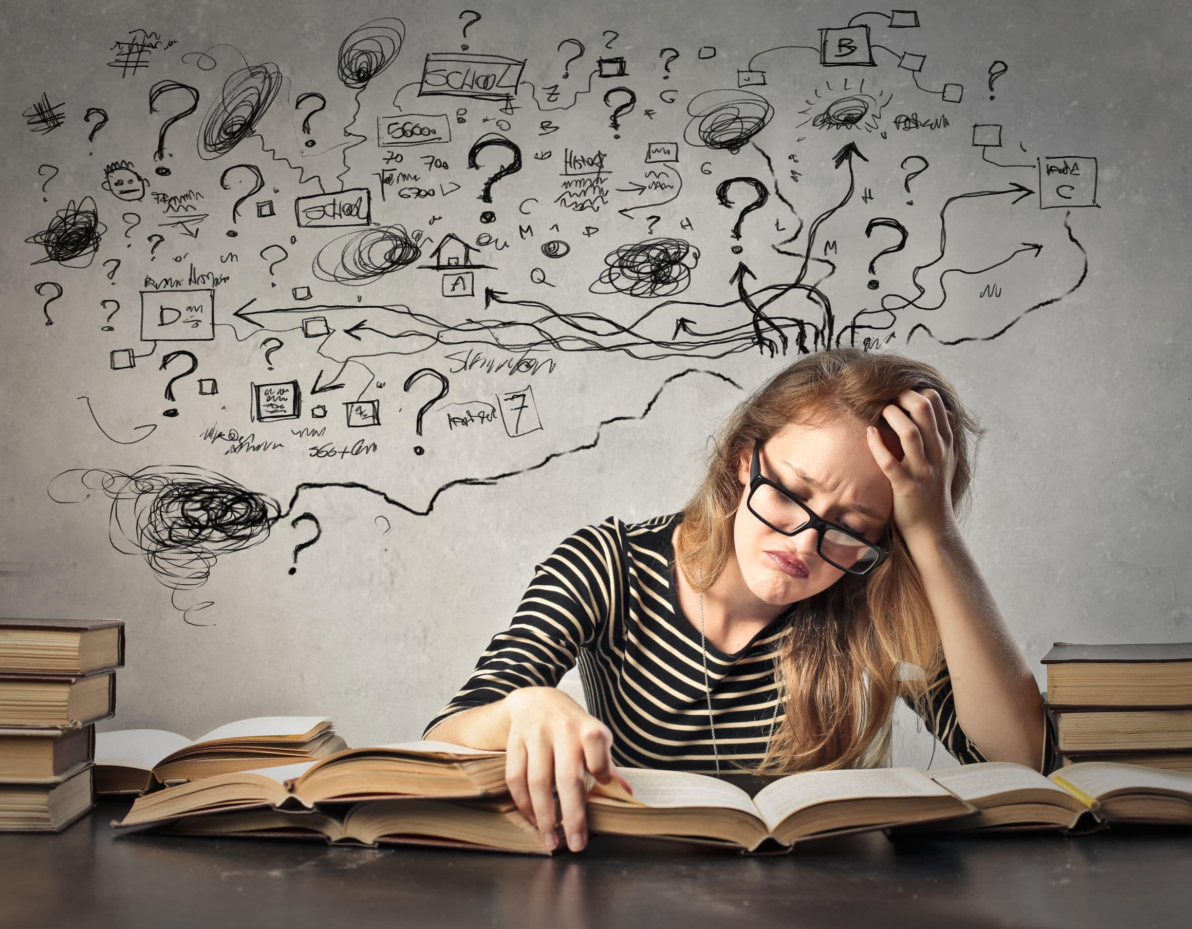 Jovem branca e loira triste e frustrada com livros abertos em cima de uma mesa, com desenhos de símbolos confusos desenhados na parede do fundo.
