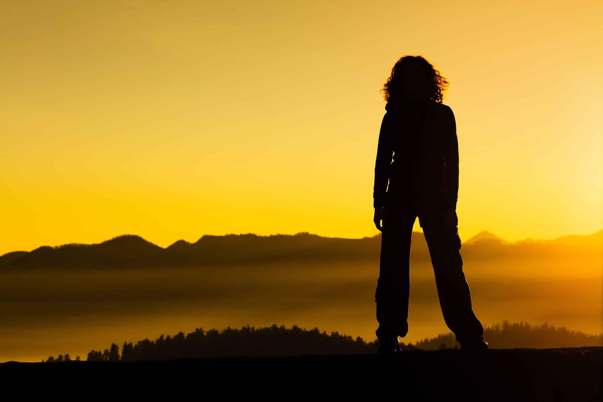 Silhueta de mulher em pé em cima de montanha observando o horizonte com o pôr do sol.