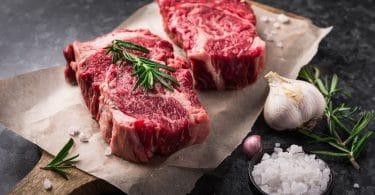 Dois bifes de carne vermelha postos em cima de papel vegetal e uma tábua de madeira. Sal grosso, alho e alecrim ao lado.