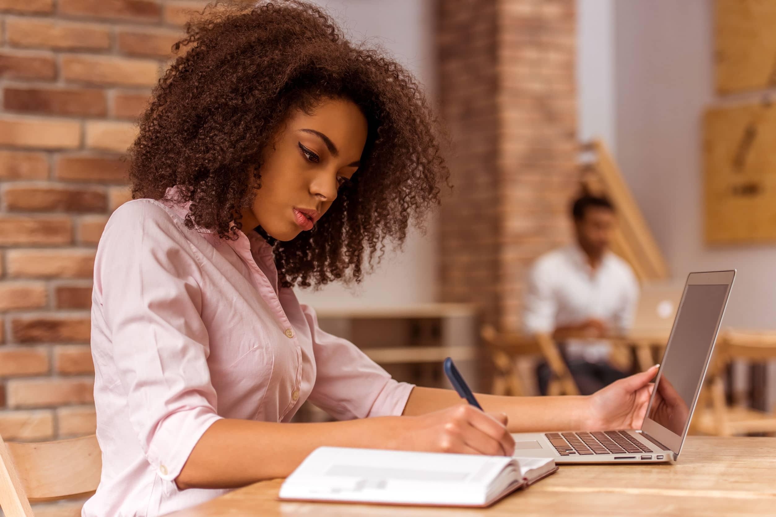 Mulher negra com blackpower usando uma camisa rosa e mexendo no computador enquanto escreve algo em um caderno.