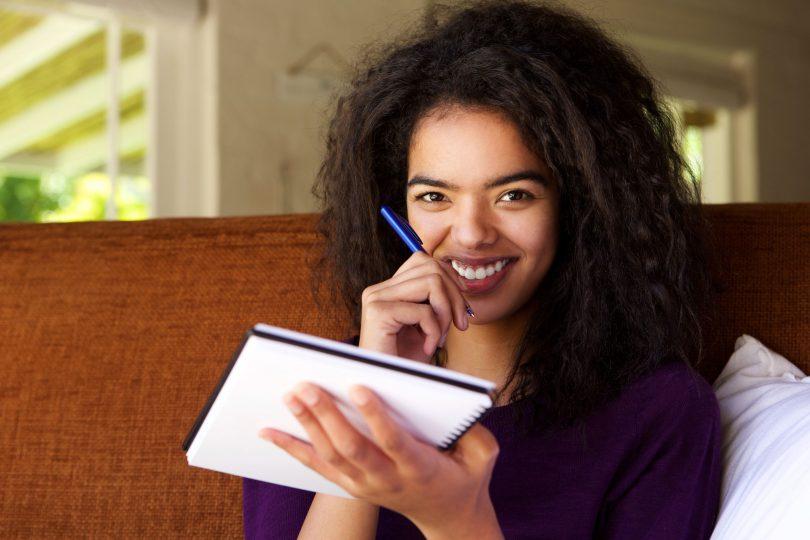 Mulher negra escrevendo em um caderno com um sorriso no rosto.