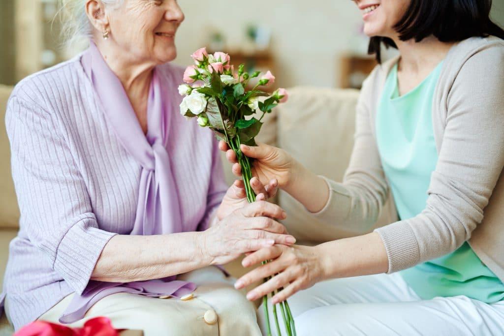 Mulher sentada em sofá entrega rosas a outra mulher mais velha.