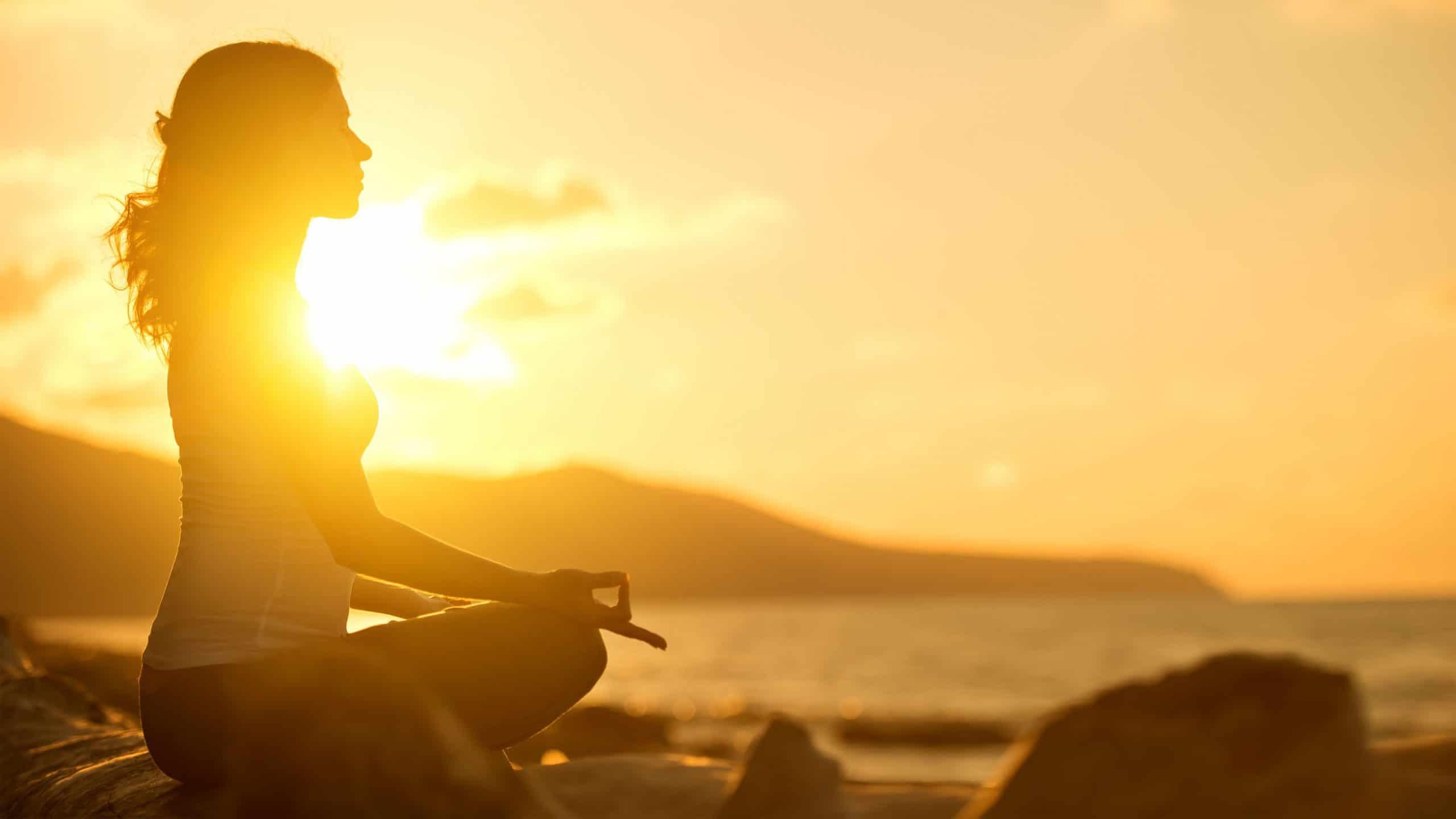 mulher meditando em pose de lótus na praia ao pôr do sol