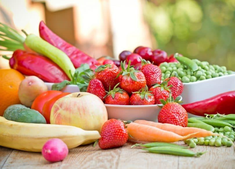 Frutas e verduras naturais em cima de uma mesa de madeira.