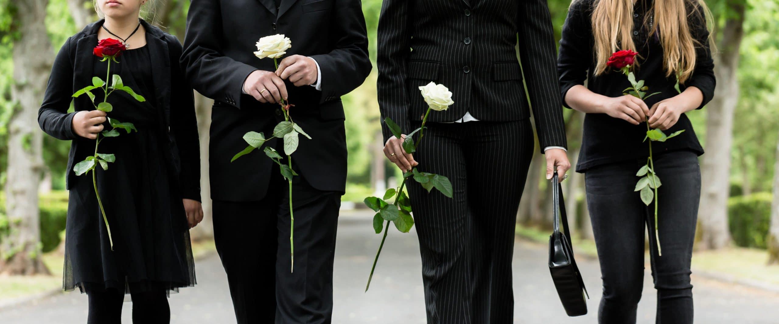 Torso da família em luto cemitério segurando rosas vermelhas e brancas nas mãos.