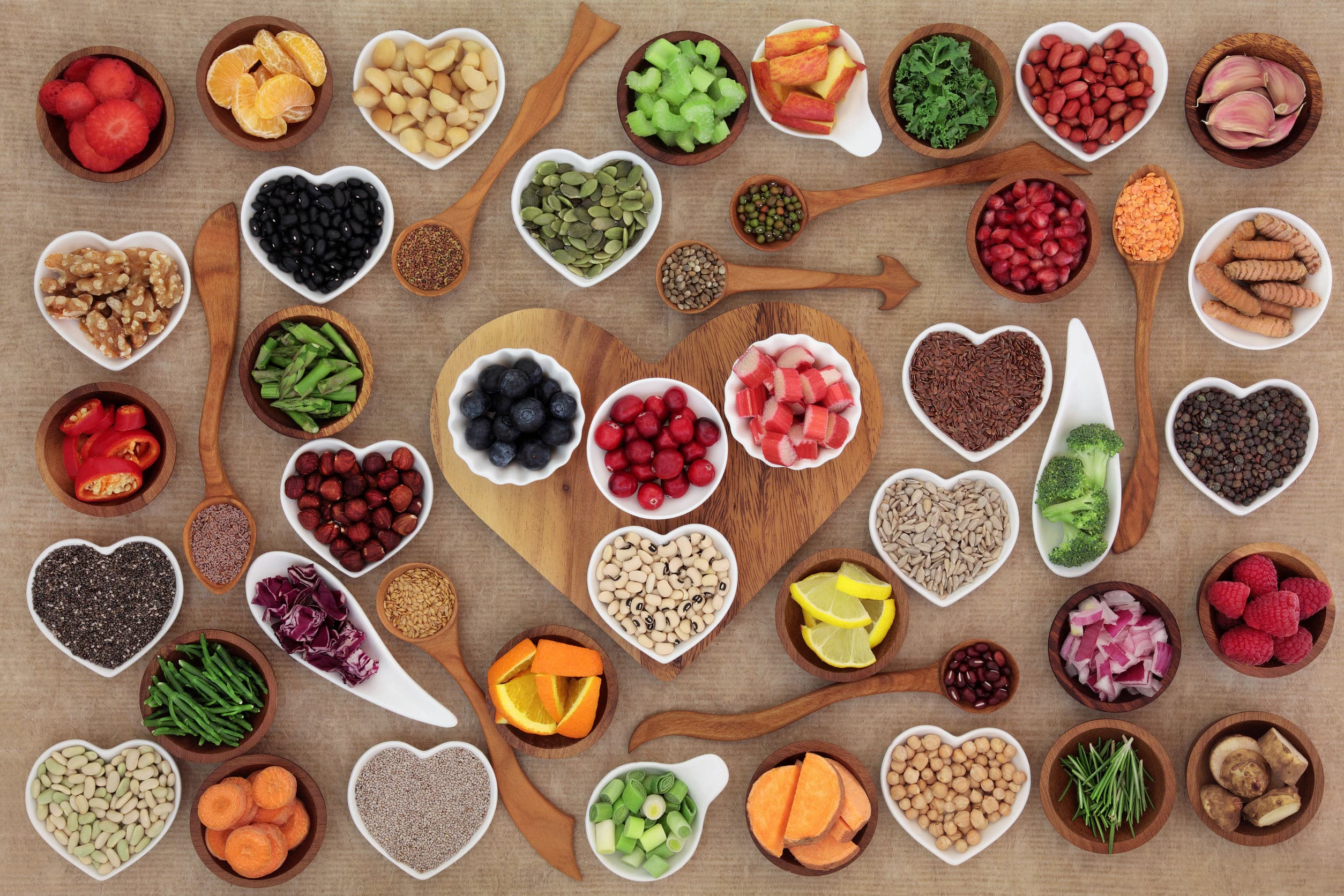 Seleção de comida super saudável em tigelas e colheres de porcelana de madeira e porcelana. Rico em antioxidantes, vitaminas, minerais e antocianinas.