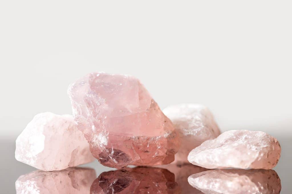 Cristais rosa claro dispostos em uma mesa, o do centro é maior que os demais. O nome da pedra é Quartzo Rosa.