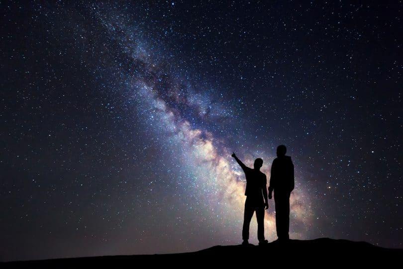Silhueta de um pai e um filho que apontam o dedo no céu estrelado da noite no fundo da Via Látea.