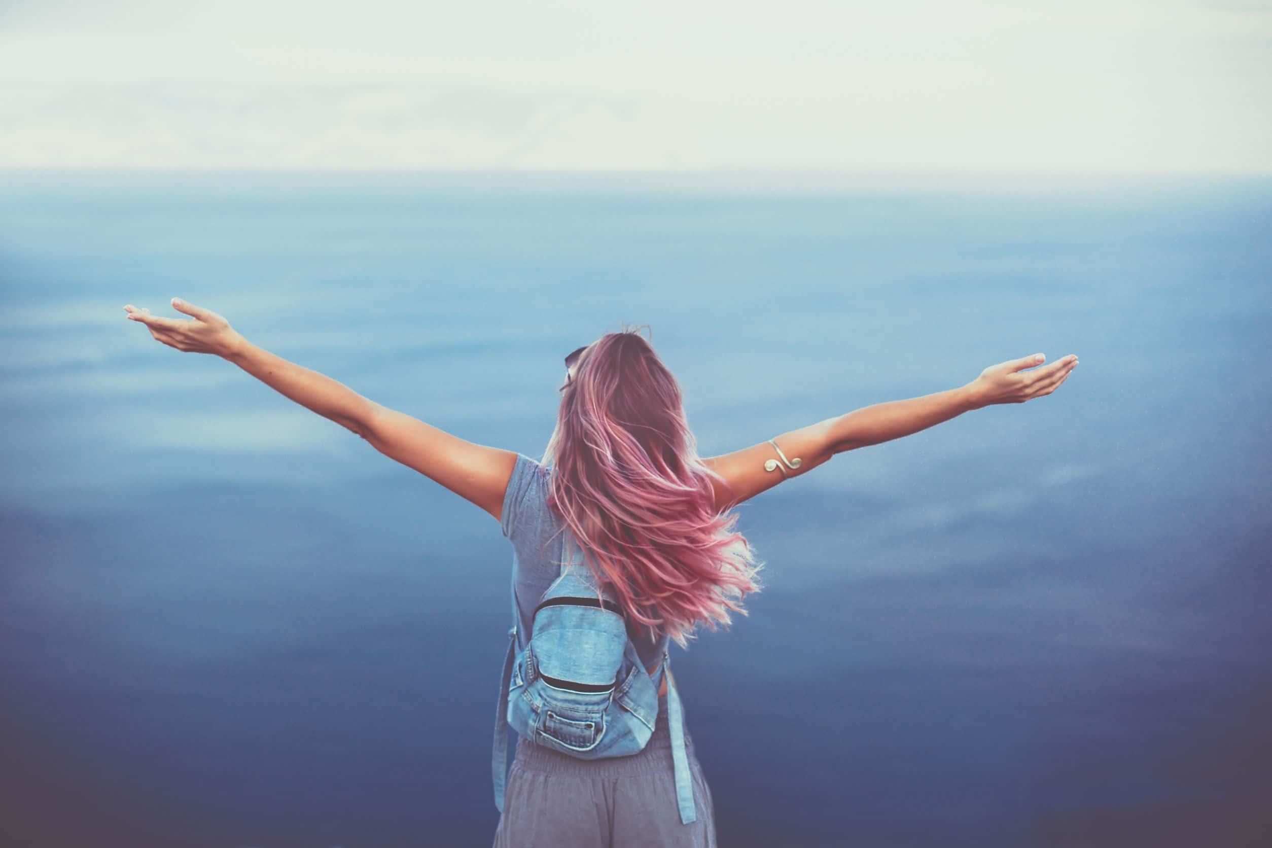 Mulher com cabelo rosa com os braços abertos. Usa uma mochila azul e roupa cinza. De frente para ela está o oceano.