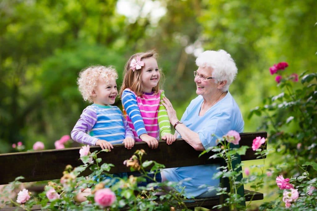 Avó e netas em um canteiro de rosas.