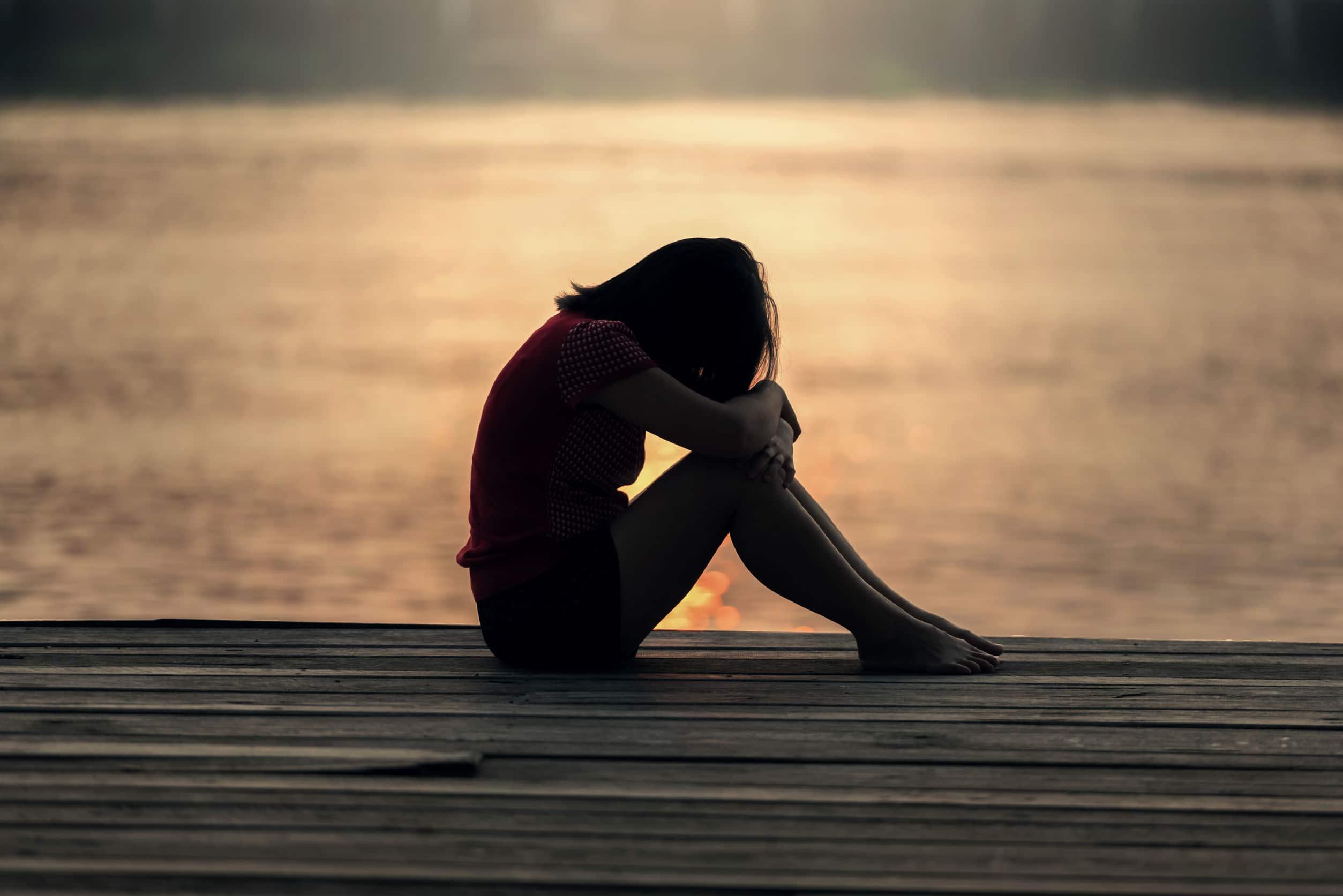 Silhueta de uma mulher preocupada e triste em um cais durante o pôr-do-sol.