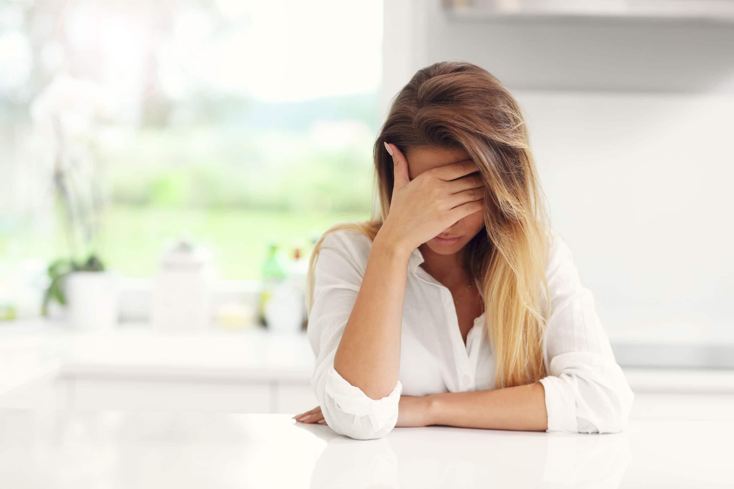 Fotografia de uma mulher triste ou pensativa na cozinha.