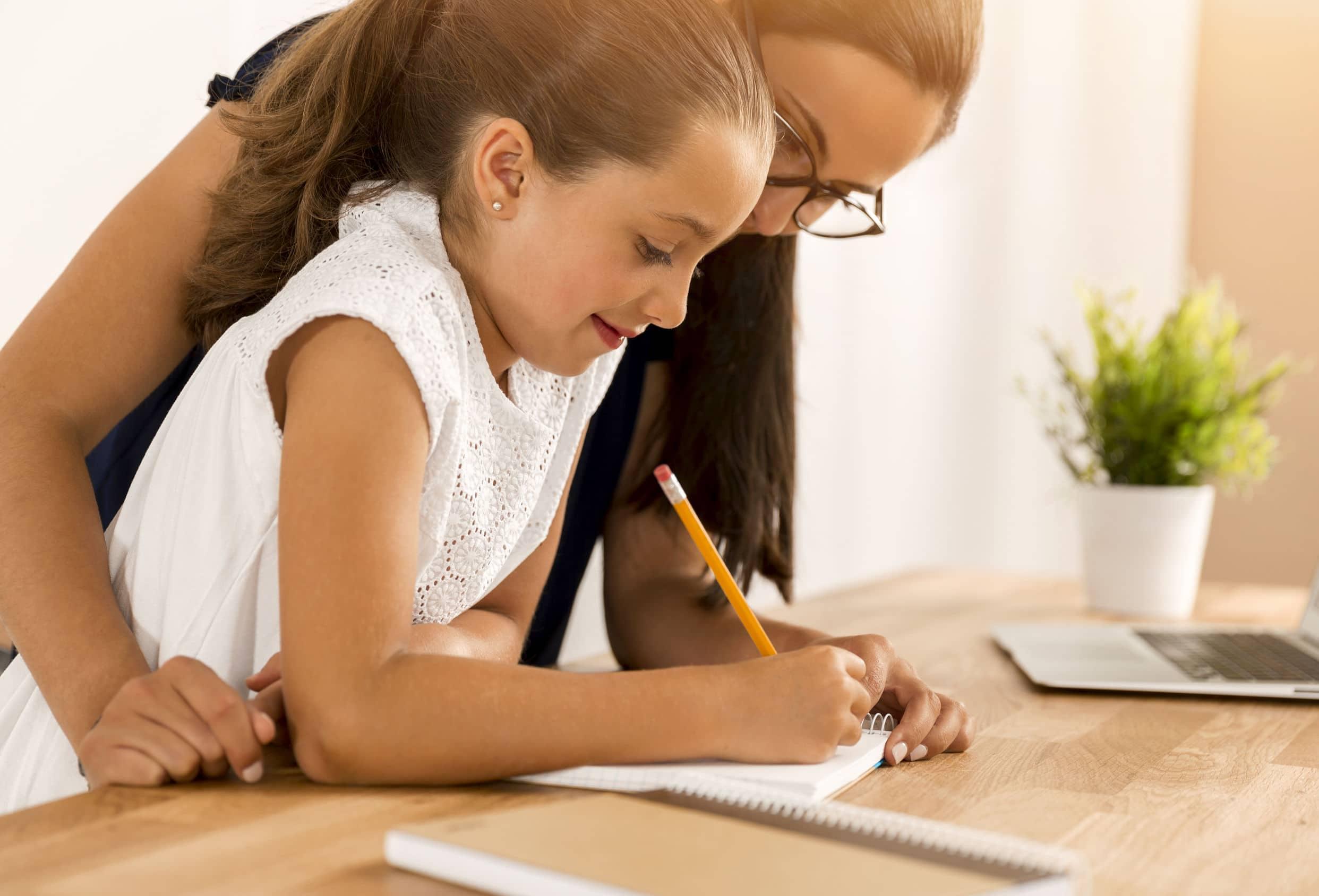Menina fazendo lição e casa junto com a mãe.