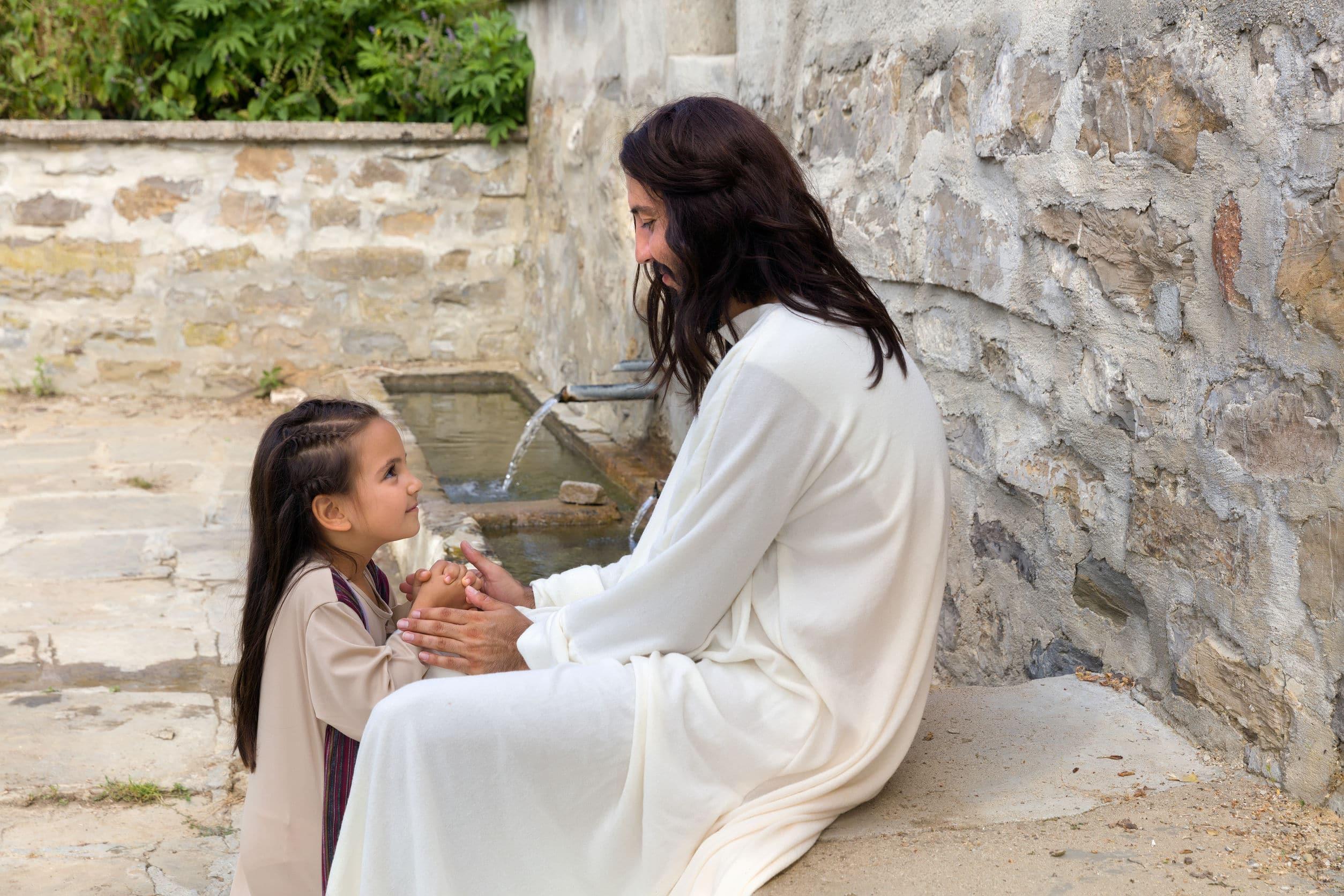 Criança vestida com vestes antigas de mãos dadas com um homem vestido de jesus, sentados perto de uma fonte de água.