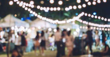 Foto desfocada de feira de festividades com muitas luzes.
