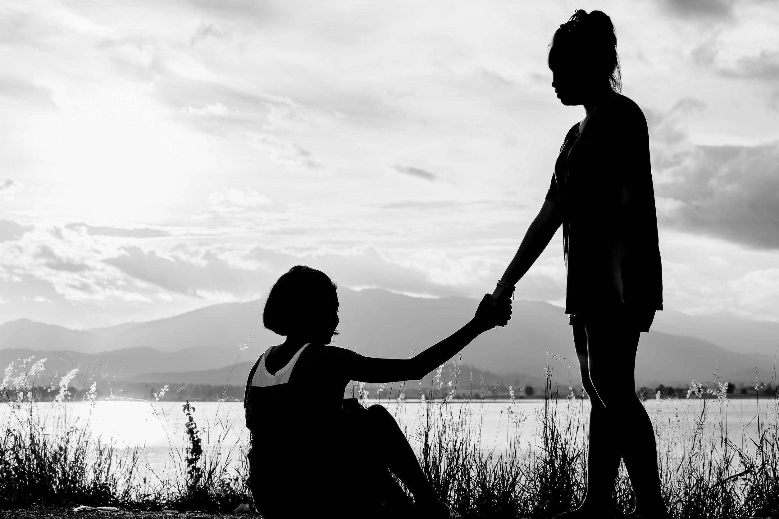 jovem menina ajuda outro menina a levantar, com lago ao fundo e vista de pôr do sol