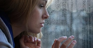 Mulher triste olhando através da janela em um dia chuvoso.