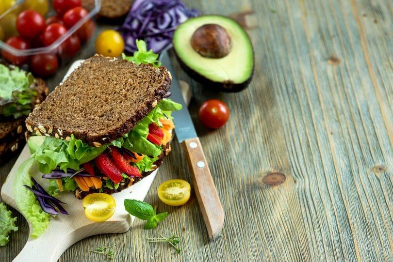 Sanduíche vegano com ingredientes frescos: abacate, alface, tomate, cenoura, repolho roxo e uma faca.