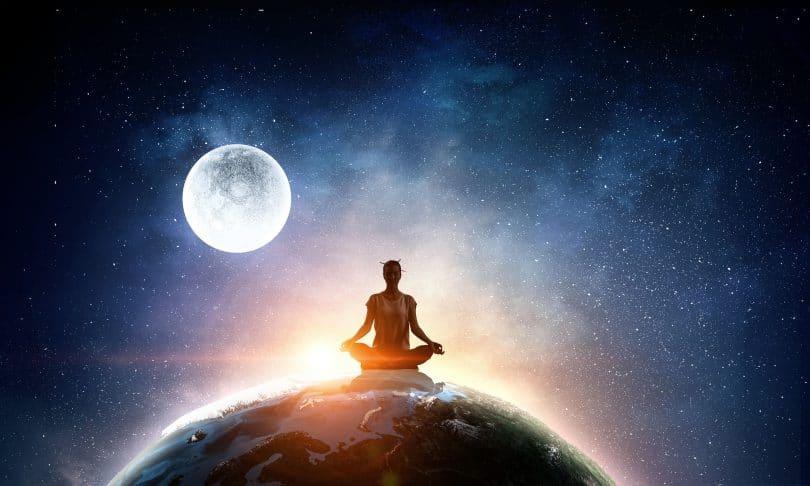 Mulher sentada em cima do planeta terra em pode de meditação. Atrás dela está a lua.