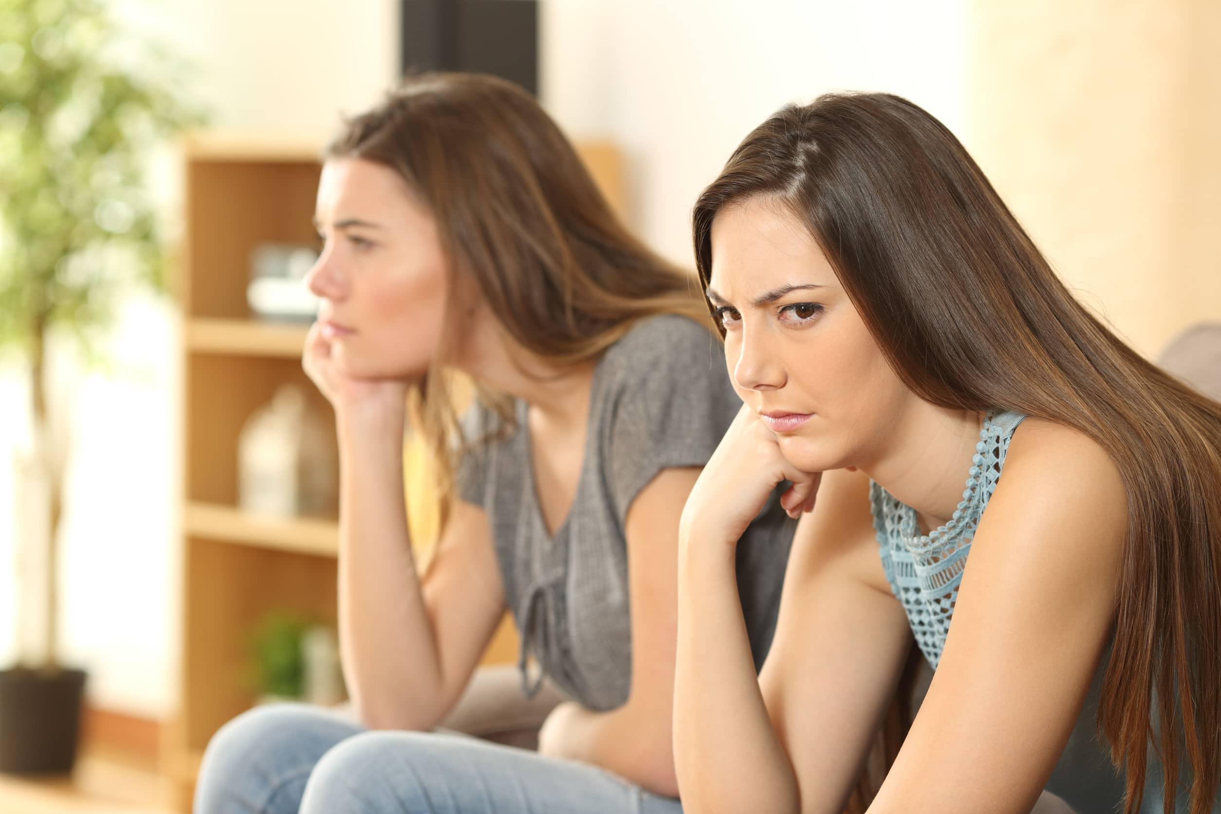 Amigas sentadas em sofá de sala de estar bravas uma com a outra
