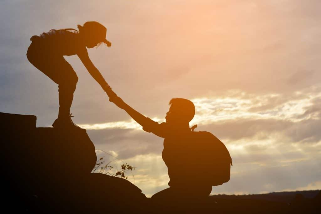 Mulher puxa a mão de um homem que tenta subir uma montanha.