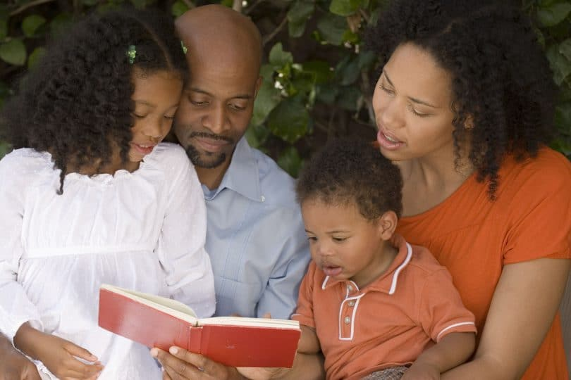 Família de afrodescendentes composta por pai, mãe, filha e filho lendo um livro no jardim.