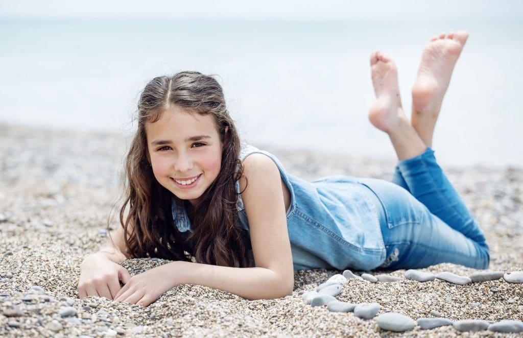 Menina deitada na areia de uma praia com cabelos escuros, bula azul e calça jeans;