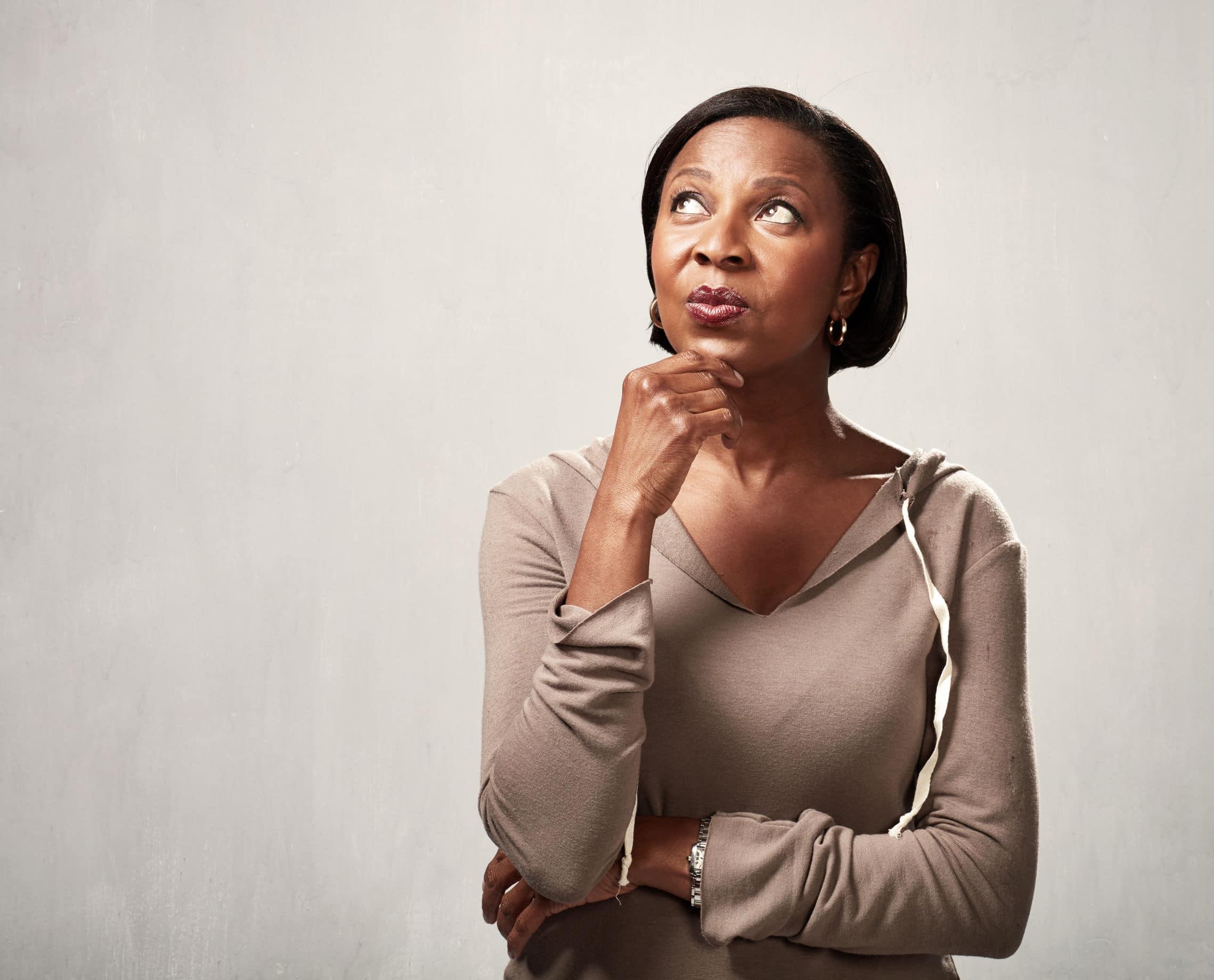 Mulher negra apoiando o rosto na mão com cara de dúvida em frente a um fundo branco.
