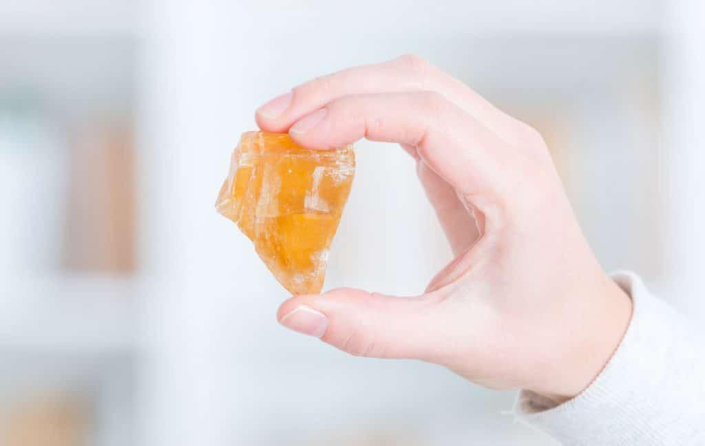 Uma mão segura uma pedra laranja de aproximadamente cinco centímetros em fundo branco. A pedra é conhecida como Calcita Laranja.