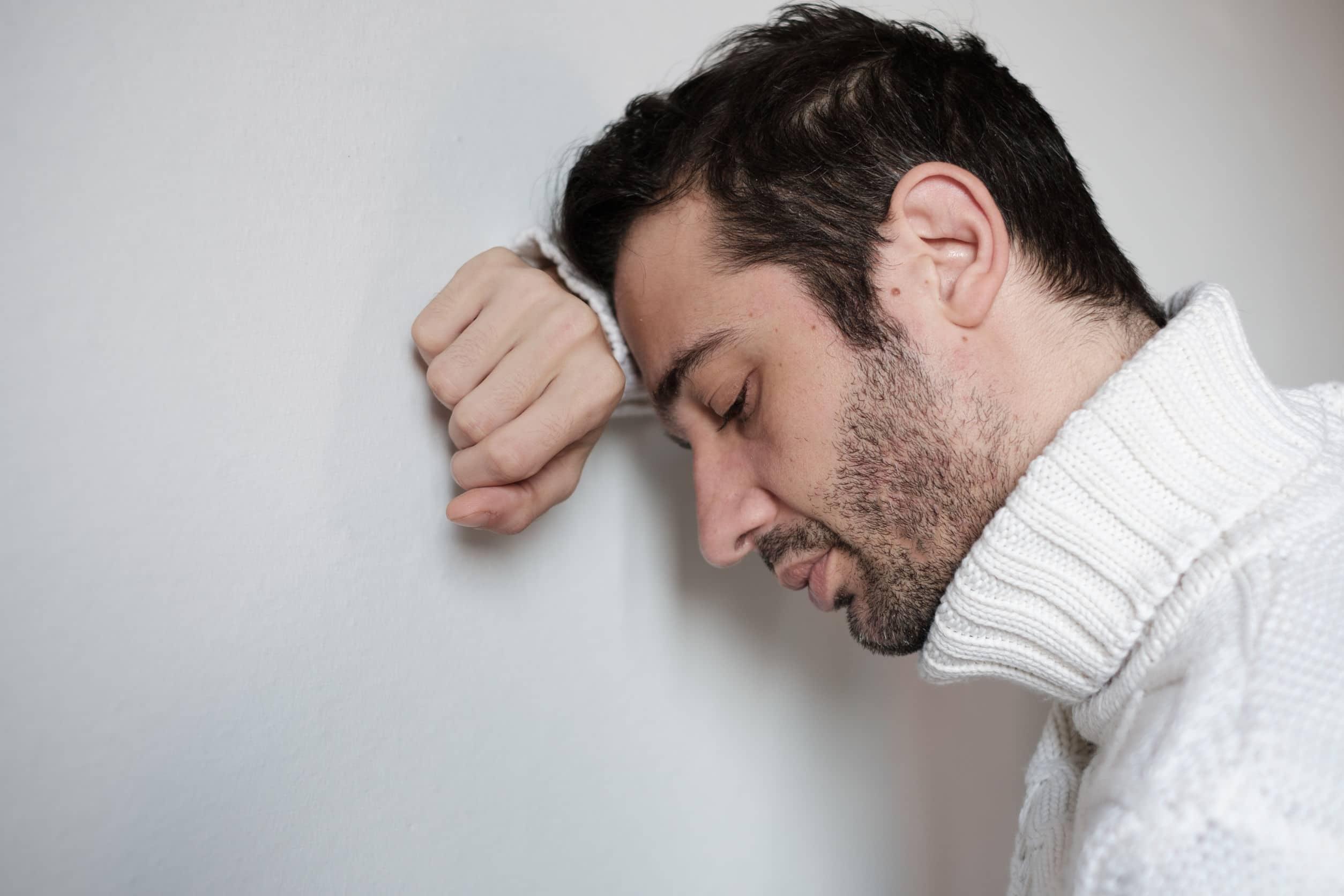 Homem usando blusa de frio com gola alta branca apoiado na parede usando uma mão. Rosto encostado na mão em sinal de tristeza e descontentamento.