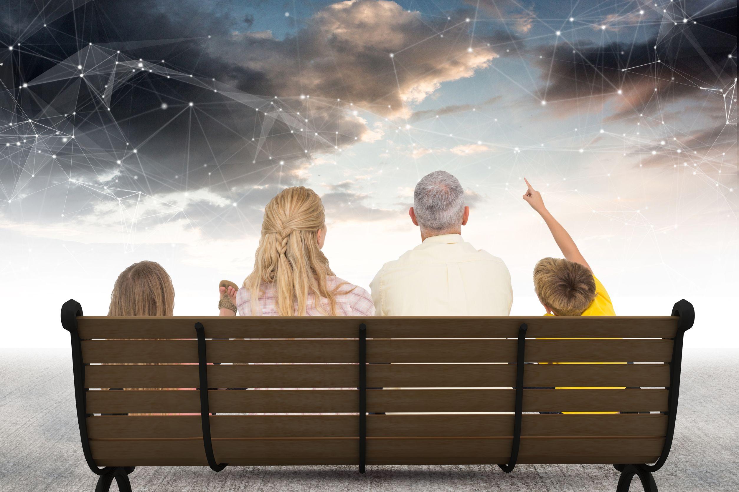 Família formada por pai, mãe, filho e filha, sentados em um banco de praça observando o céu da tarde com constelações desenhas.