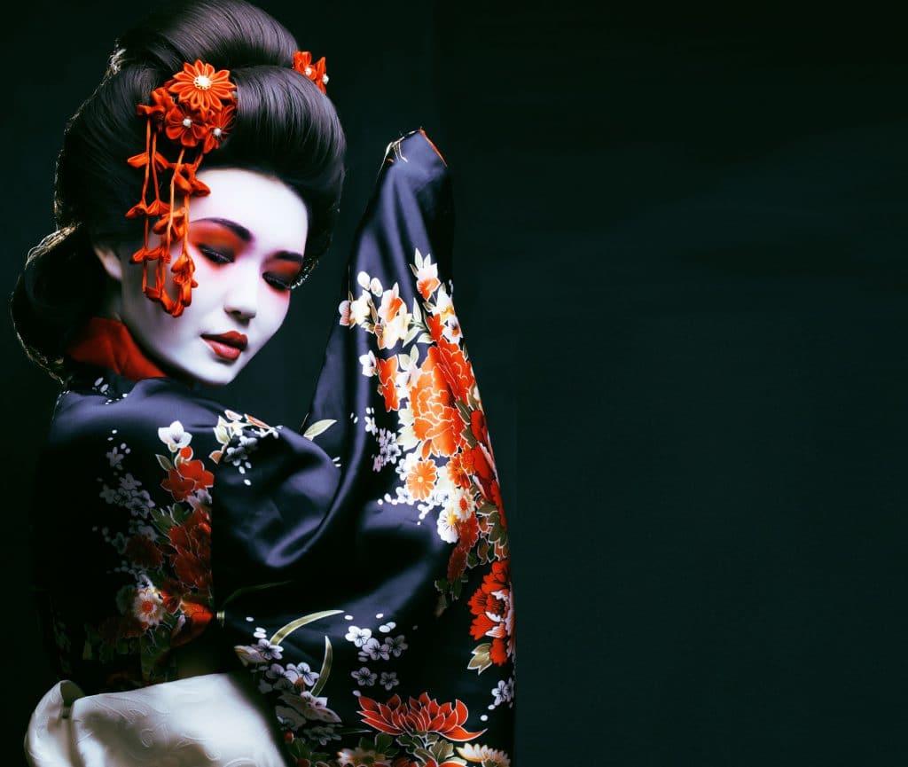 Gueixa. Uma mulher oriental vestindo um kimono com flores sakura decorando. Ela está com uma maquiagem marcante de tons vermelhos.