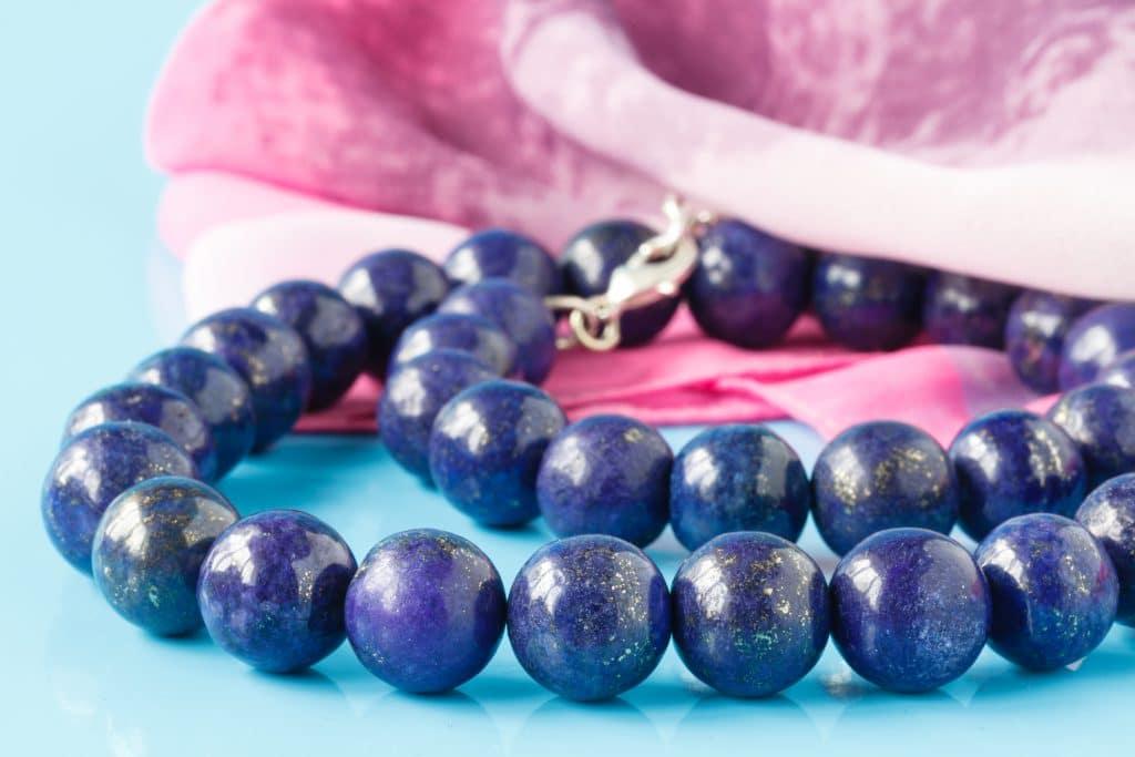 Colar de pedras redondas azuis com pequenos detalhes em dourado, sob um pano rosa e uma mesa turquesa.