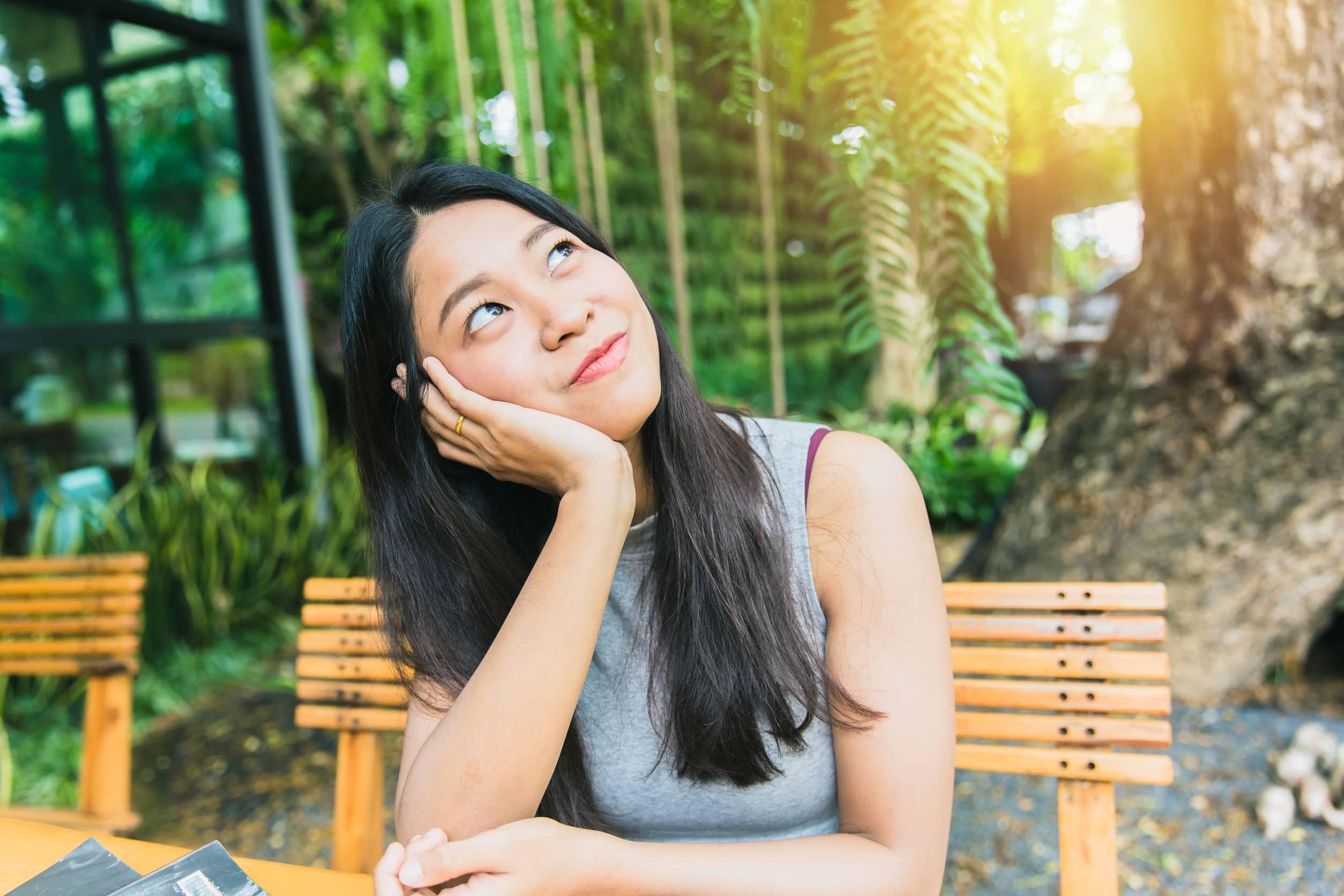 Menina asiática pensando em algo, sentindo saudade de algo. Ela apoia o rosto com a mão e olha para cima.